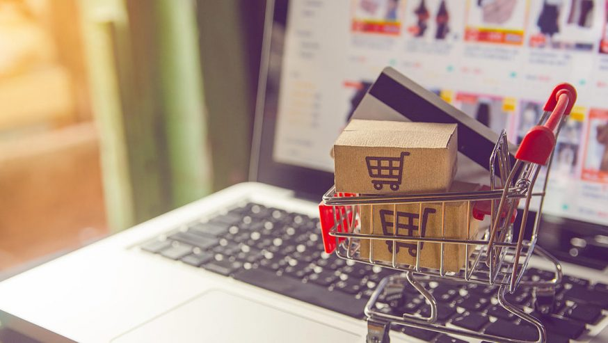 Shopping online concept – Parcel or Paper cartons with a shopping cart logo in a trolley on a laptop keyboard. Shopping service on The online web. with payment by credit card and offers home delivery.
